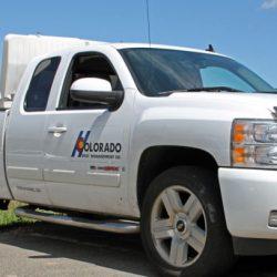 科罗拉多州害虫管理人员从一辆白色工作卡车上拿工具