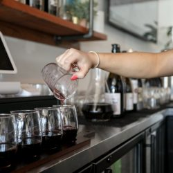 A bartender pouring four glasses of red wine at 101 Wine Press wine restaurant in Salinas