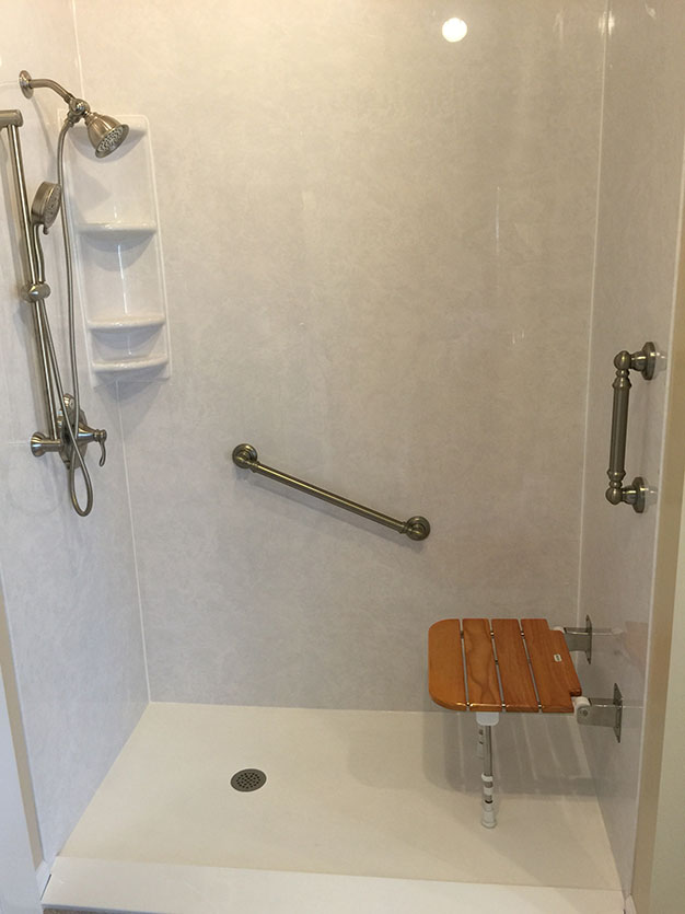 A white walk-in shower with safety handles and a bench by Bathmaster