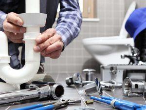 Plumber installing pipes underneath a bathroom sink.