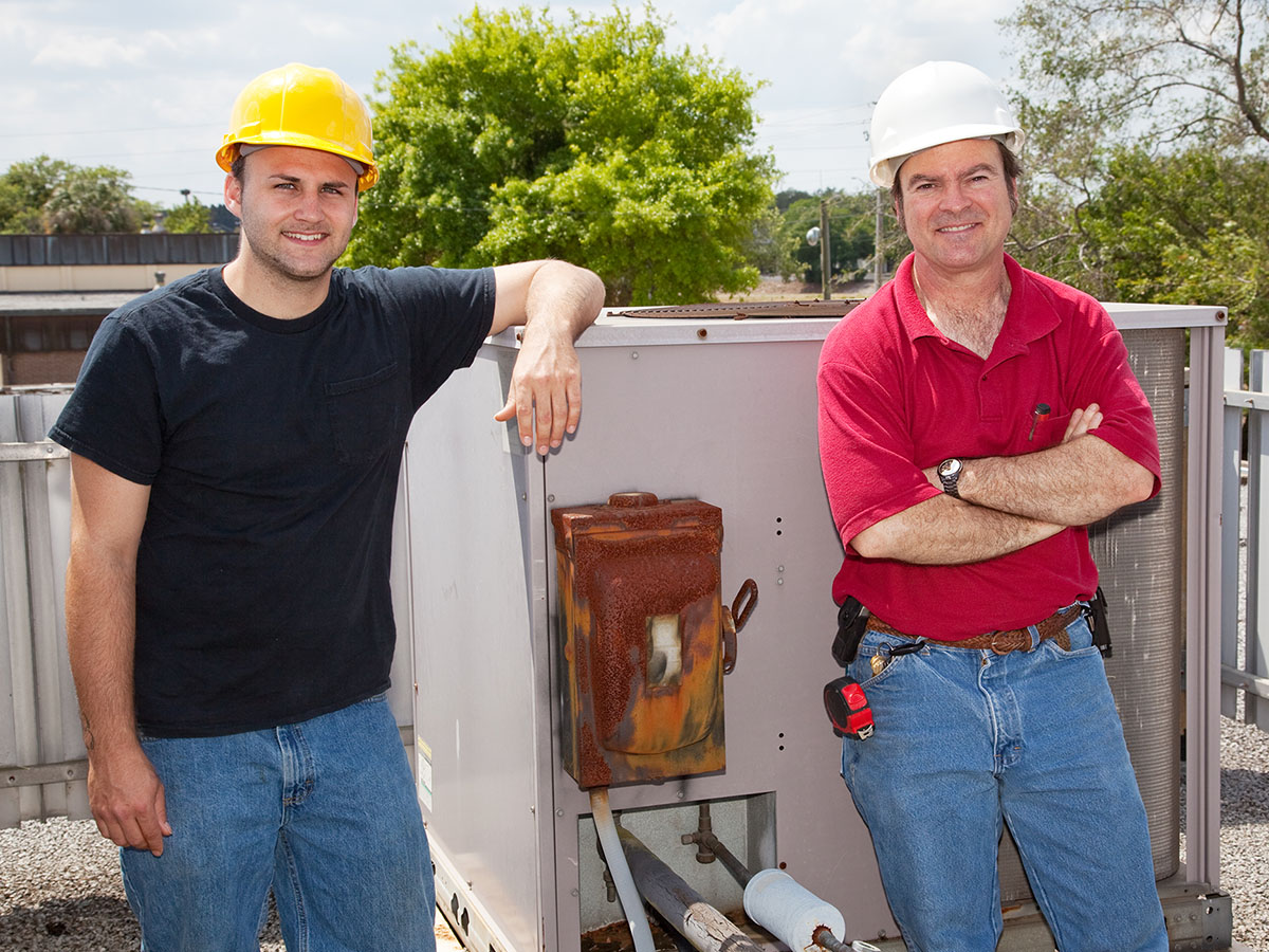 Two men wearing hard hats, leaning up against an HVAC unit and smiling.