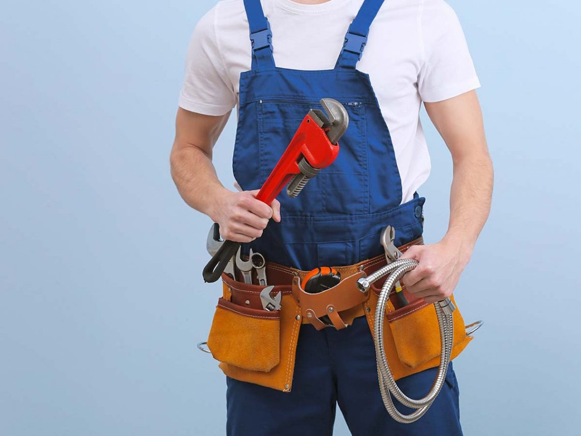 An image of a plumber holding a wrench and wearing a tool belt.