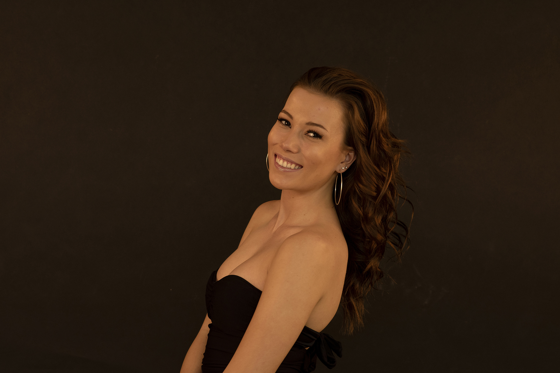 Model (Rebecca) smiling in black halter top, with a dark background