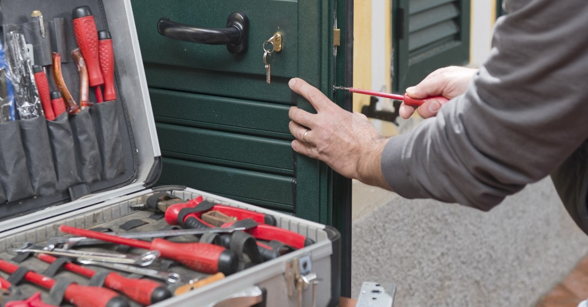 Image of a locksmith working at a home.