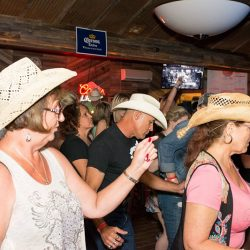People dancing with cowboy hats at our local restaurant - The 4 Way Bar and Grill