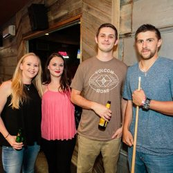 Four people with drinks and pool sticks at our bar with pool tables - The 4 Way Bar and Grill