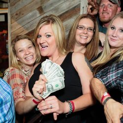 Woman and friends with money at our bar and grill - The 4 Way Bar and Grill
