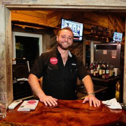Smiling server behind a table at our bar and grill - The 4 Way Bar and Grill
