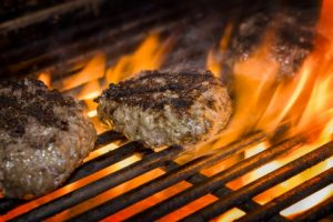 Premium beef burgers flame-broiled on a gas grill.
