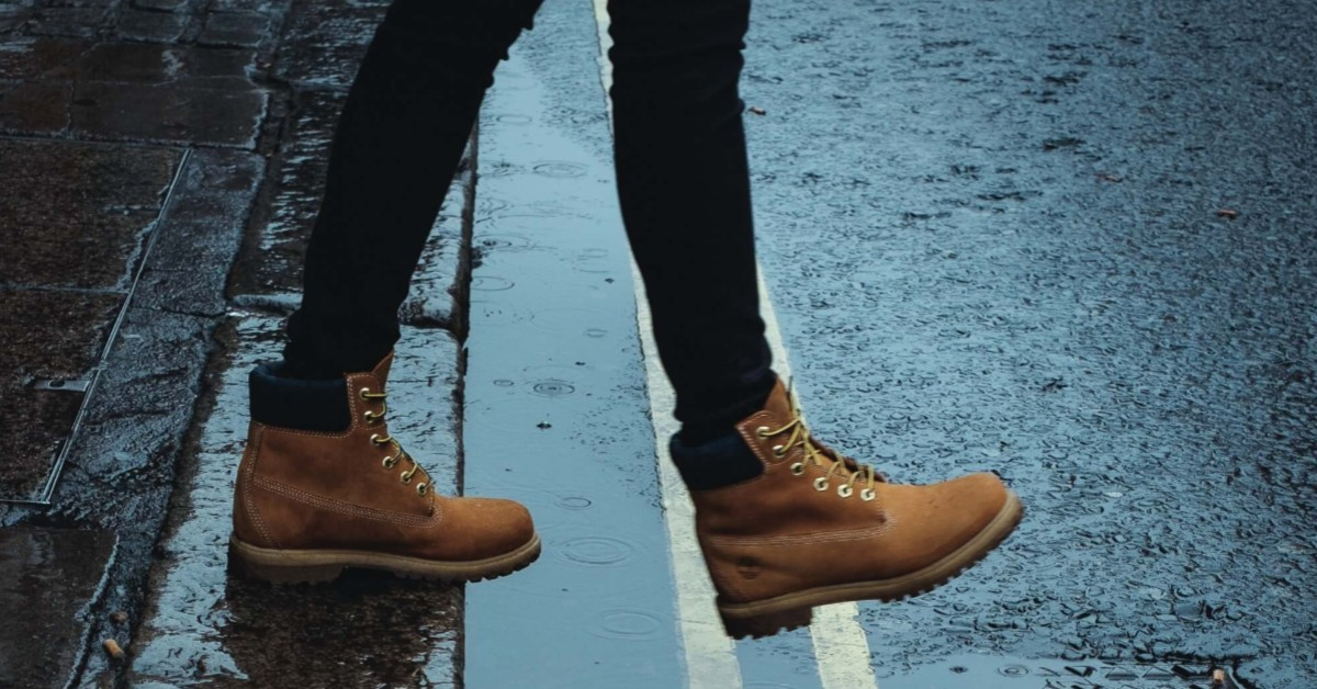 Image of a person wearing boots stepping into a wet street.