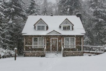 Image of a warm house covered in snow and surrounded by trees.