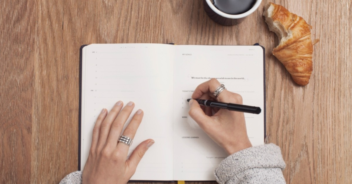 Image of a woman writing in her goal planner with a cup of coffee and a croissant on the side.