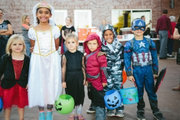 Group of kids standing and smiling in Halloween costumes.