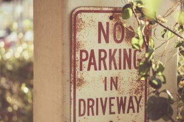 """Image of a vintage sign that reads """"No Parking in Driveway."""""""