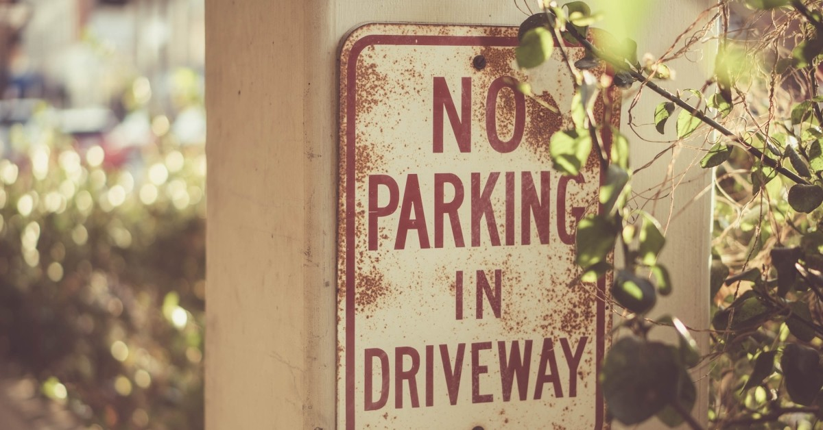 "Image of a vintage sign that reads ""No Parking in Driveway."""