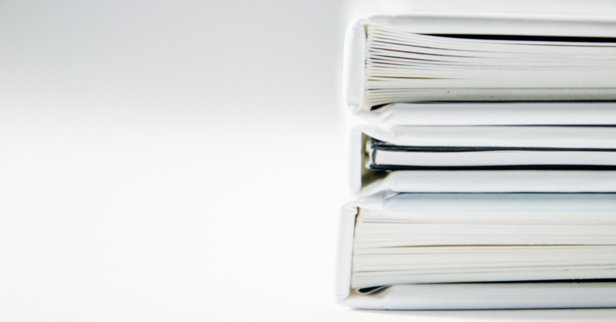 Image of stacked binders full of papers.