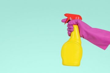 Image of a person wearing a pink rubber glove and holding a spray bottle with a cleaning solution.