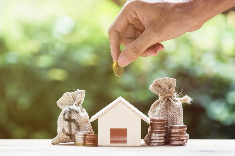 A man hand putting money coin over small residence house and money bag with nature background. A sustainable investment