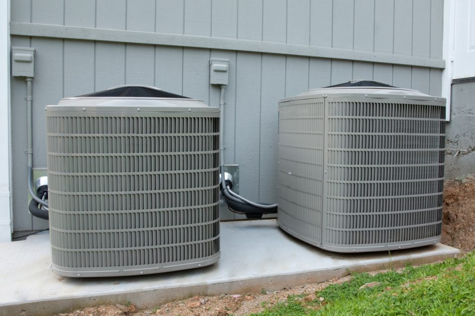 Two electric residential heating and air conditioning (HVAC) packaged heat pump units on a concrete pad