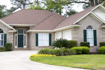 A nice brick house and landscaped lawn with a cracked concrete driveway