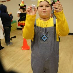 A child with autism shows off the candy he received while participating in Halloween activities.