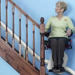 Woman on Stairlift With Blue Wall Background