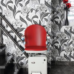 Red Stairlift Chair Seat In Front of Patterned Wall