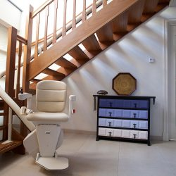 White Stairlift at the Base of Wooden Stairs