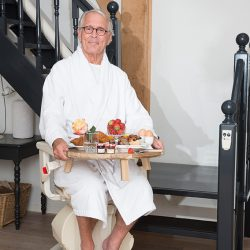 Elderly Man Holding Breakfast Tray Sitting on Stairlift