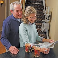 Elderly Couple Reading Newspaper With Stairlift in Background