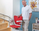 Elderly Man Next to Red Seat Stairlift