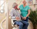 Happy Elderly Couple Next to Stairlift