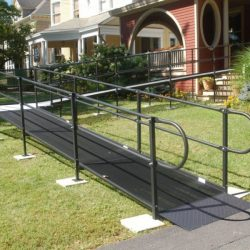 Black Metal Wheelchair Ramp Leading to Red House