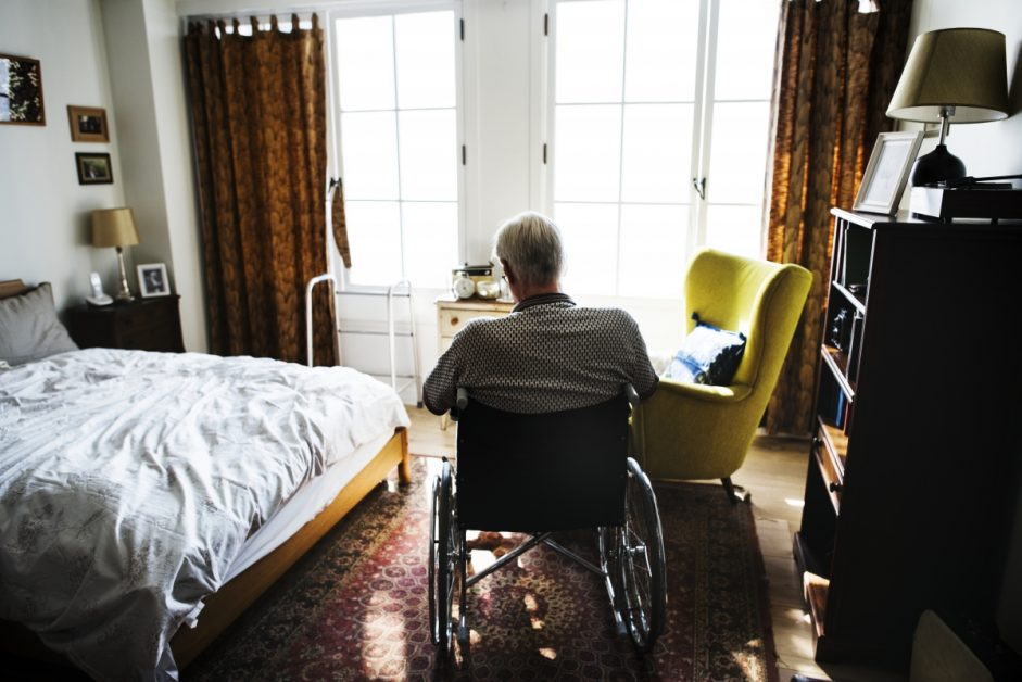 Man in Wheelchair in Bedroom
