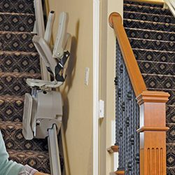 Elderly Couple Near Stairlift, Woman Riding Stairlift