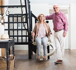 Older Couple Standing Near Curved Rail Stairlift