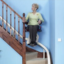 Woman Riding Curved Rail Stairlift