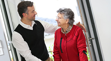 Man Greeting Senior Woman
