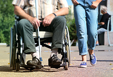 Woman Walking Side-by-Side With Man in Wheelchair