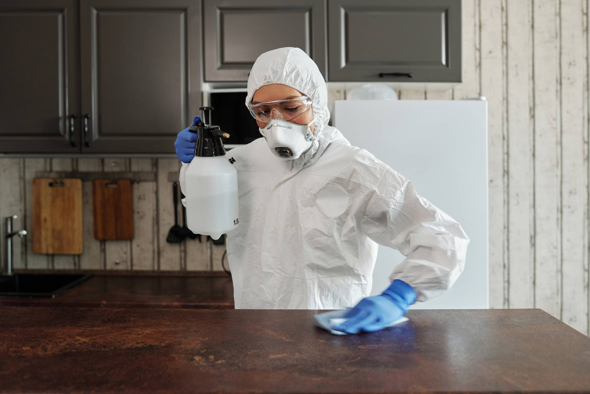 A woman in protective gear disinfecting tabletop in a kitchen