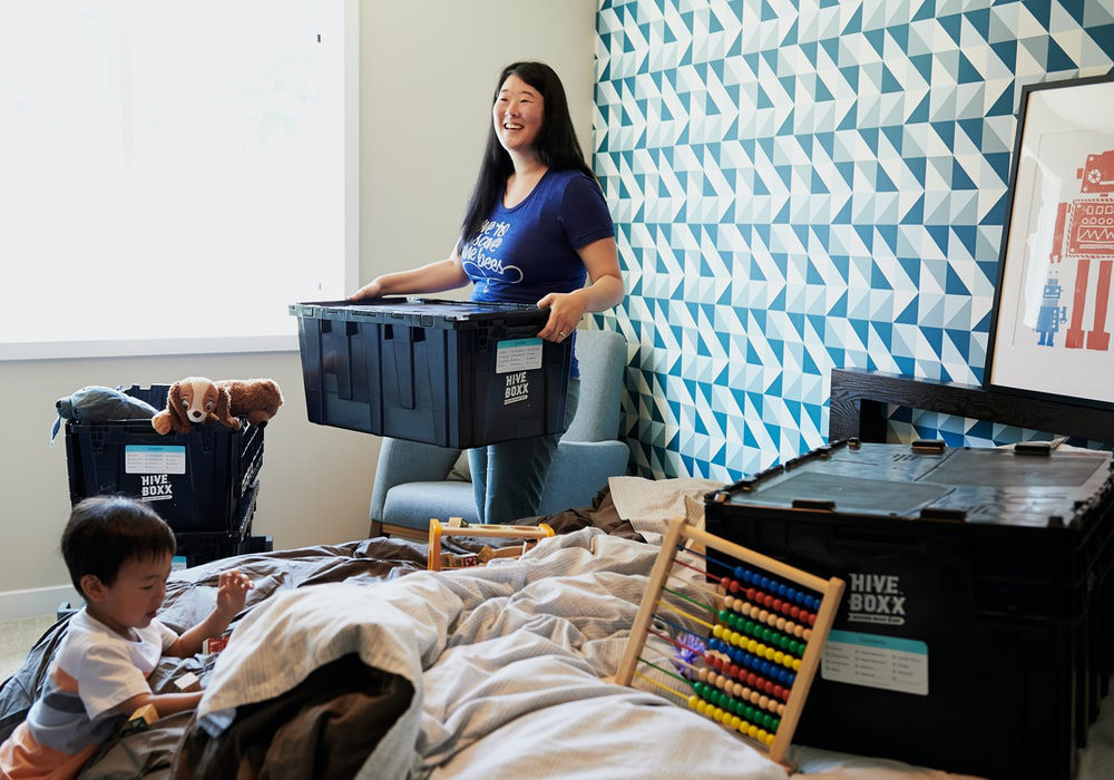 A woman carrying moving boxes with her child going through the clutter