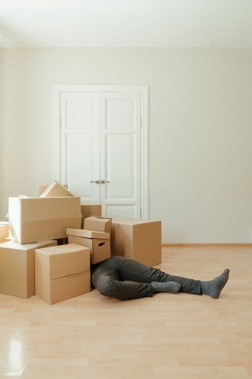 Man lying on the floor amidst packing boxes