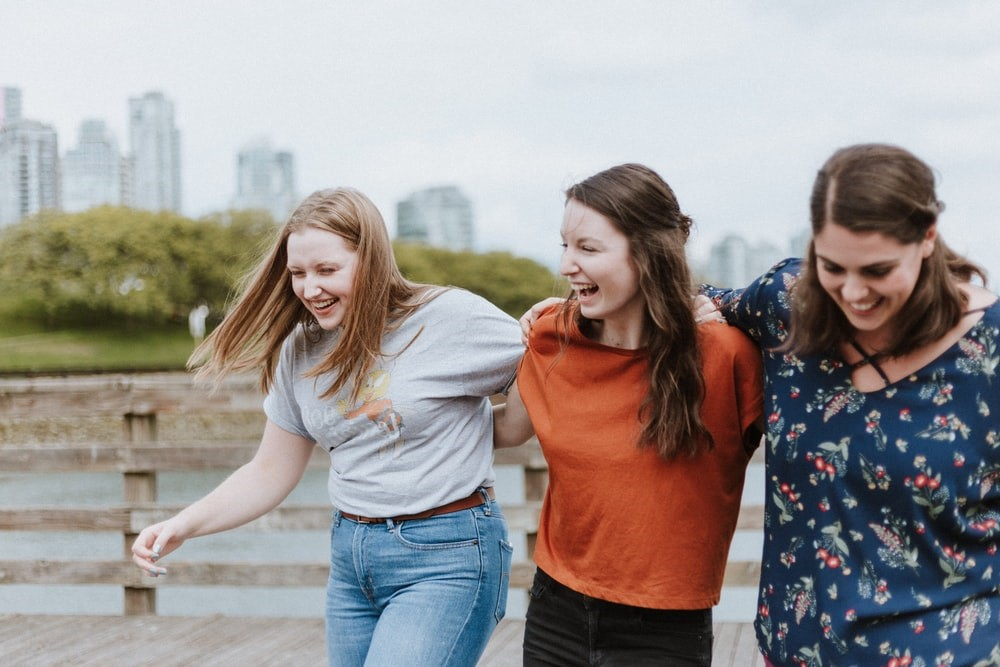 Three women happily walking arm in arm