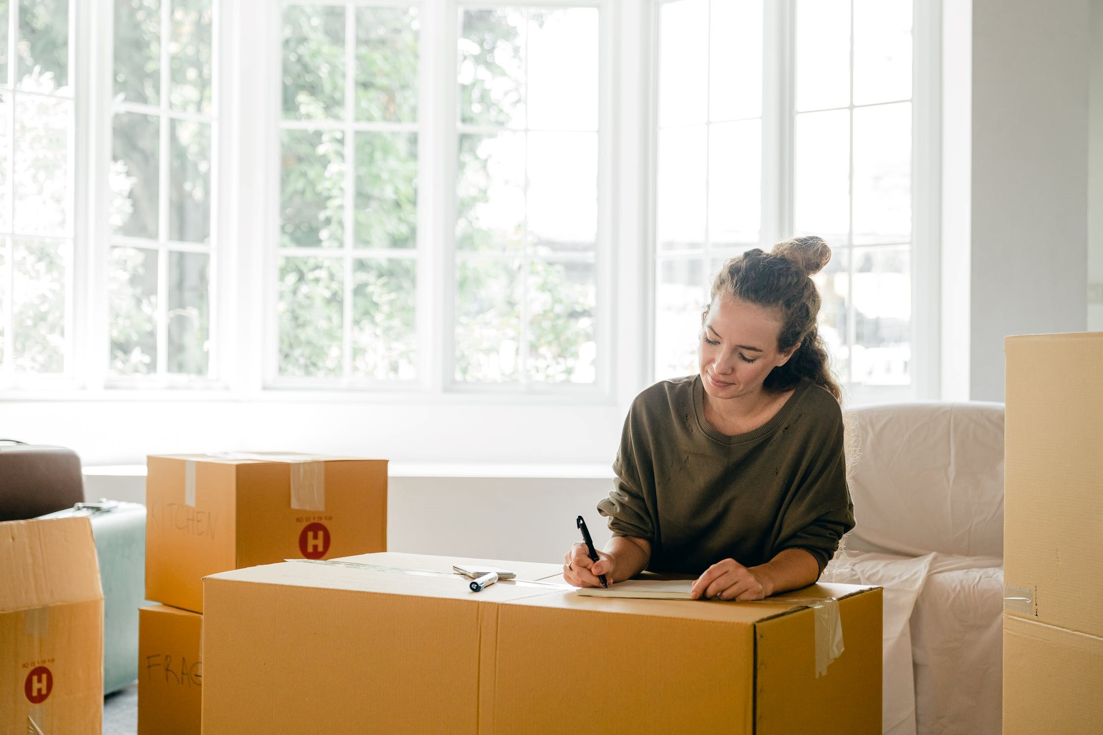 A woman writing on her notepad amid moving house