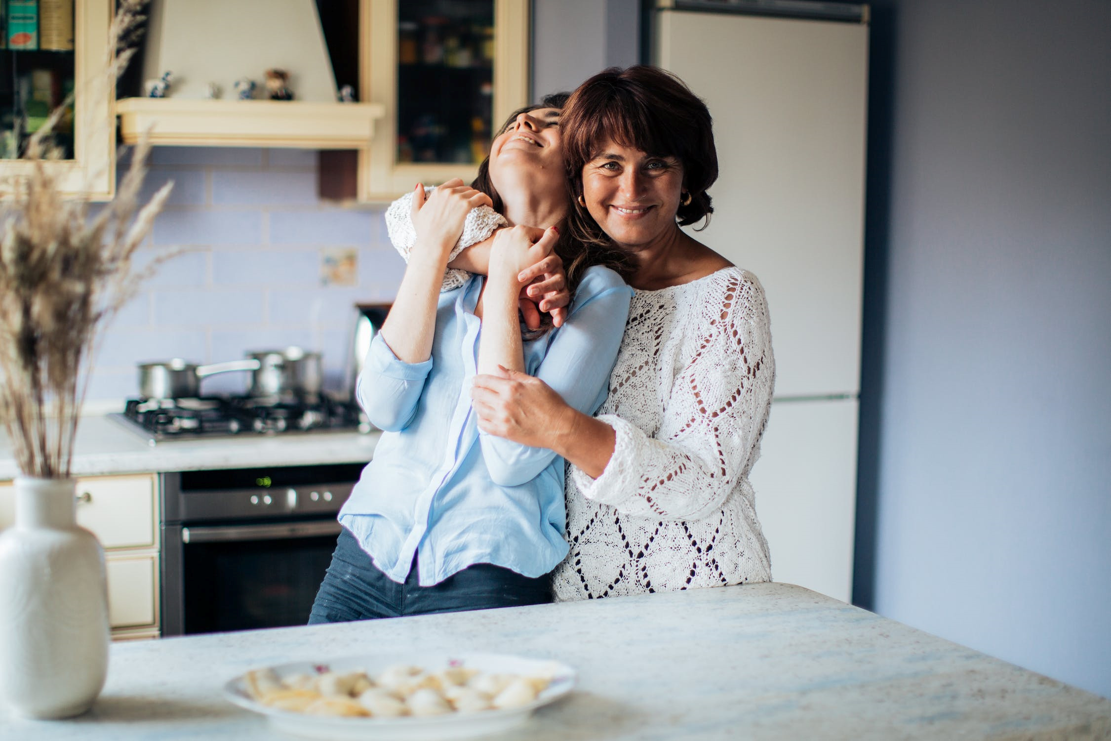 A woman hugging her daughter in a kitchen