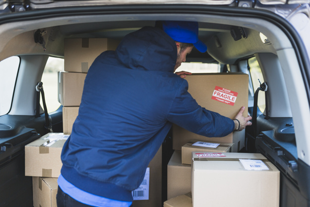 A local mover in Seattle, placing packed boxes in the van, ready for the move.