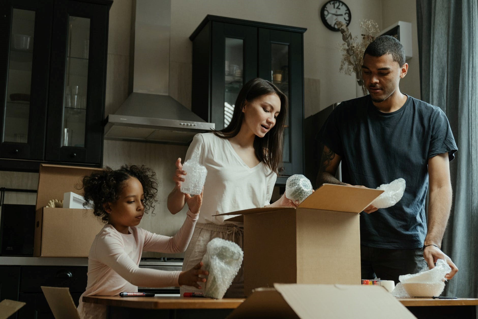 A family packs bubble-wrapped bowls and glasses into a cardboard box