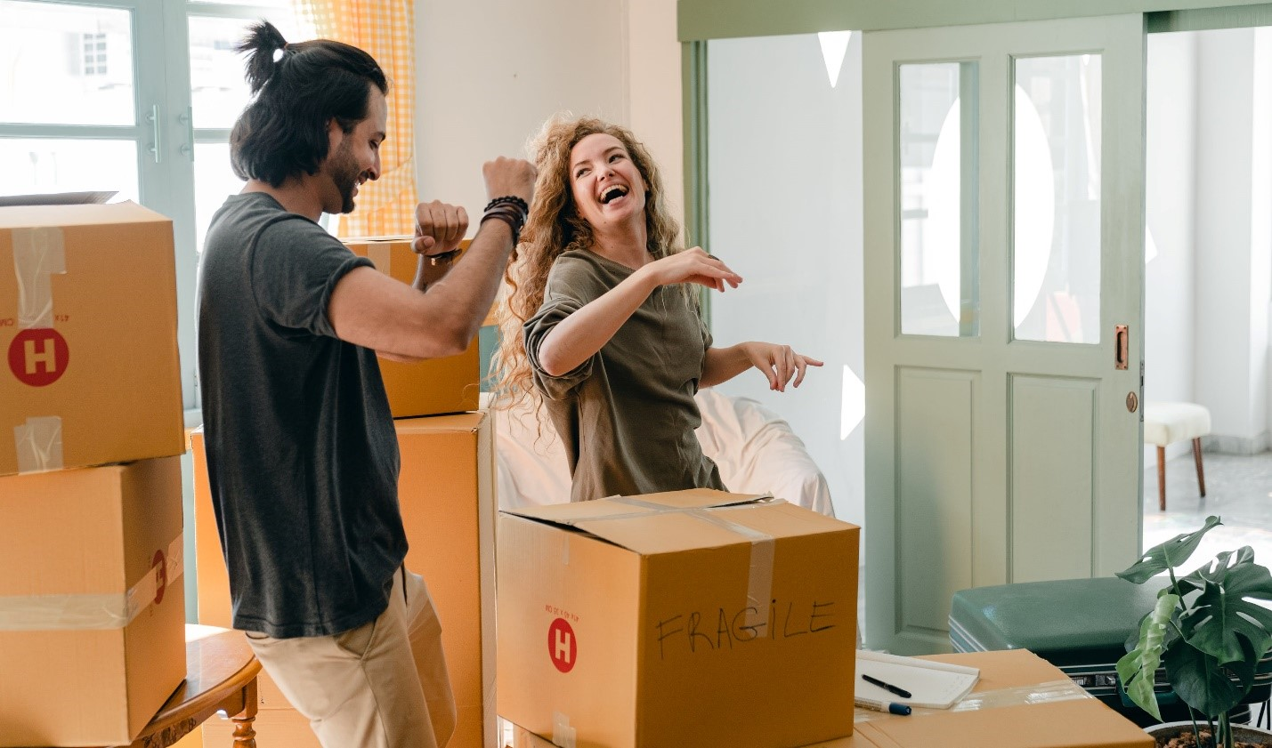 A couple laughs and dances as they unpack boxes.