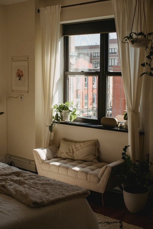 Small bedroom with a small sofa and window.