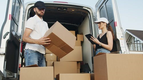 Man and woman can be seen loading cardboard boxes in a van.